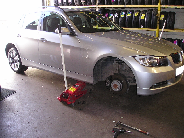 Car undergoing tyre and wheel changing
